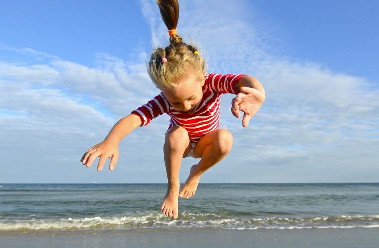 תמונת אווירה ילדה קופצת בחוף הים